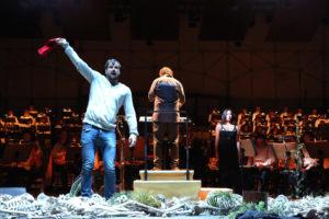 Bariton Holger Falk schwingt die rote Fahne. Marisol Montalvo, als La Mort, steht neben Dirigent Steven Sloane. Foto: Ursula Kaufmann