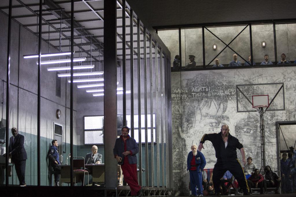 Ganz links im Käfig: Sir Willard White als Gorjančikov, Alexander Vassiliev als Gefängnisgouverneur; daneben: Štefan Margita als Luka, Graham Clarke, ein älterer Gefangener und Nickey Spencer, ein kleiner Gefangener. Foto: Bernd Uhlig