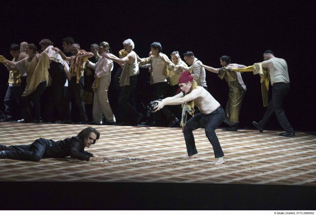 Der Narr, Andrew Nolen, hält die Aschenurne des ermordeten Vaters Hamlet, Raphael Bruck, hin. Foto: Mathias Stutte