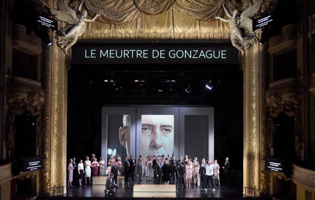 Laurent Alvaro als dänischer König Claudius an der Opéra Comique reagiert entsetzt auf den Königsmord, den Hamlet von Komödianten inszenieren lässt. Stéphane Degout als Hamlet hebt die Arme und klagt an. Foto: Vincent Pontet