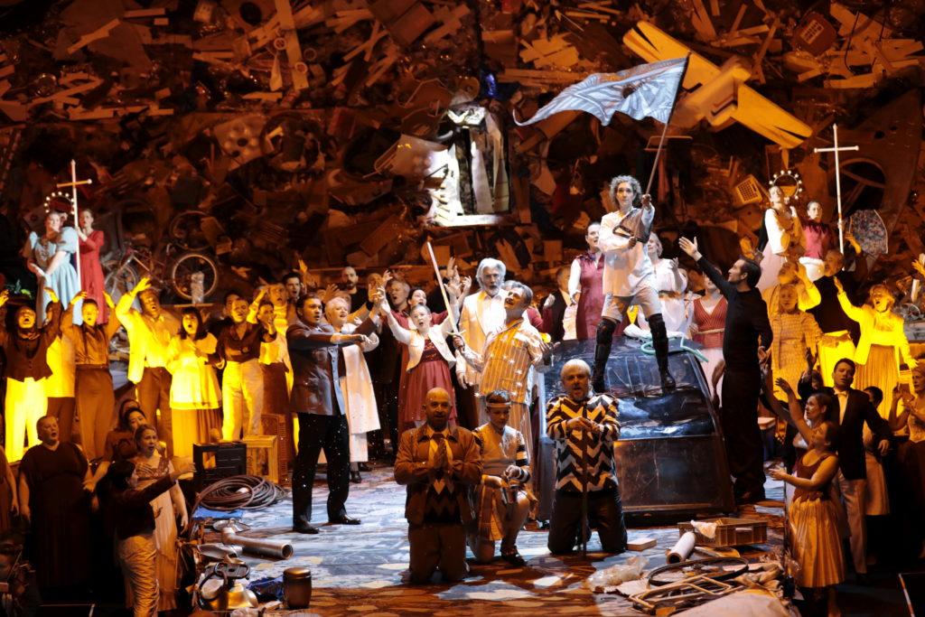 """Juliane Banse (Johanna) schwenkt die Fahne auf dem Autowrack! Davor knien John Heuzenroeder (Herzog von Alenςon), Erzengel Michael als Kind (Robert Koch) und Oliver Zwarg (Gilles de Rais, genannt """"Blaubart""""). An den Aureolen zu erkennen sind Menna Cazel (Hl. Katharina) und rechts Arnheiđur Eiríksdóttir (Hl. Margarete). Vor dem Chor und der Statisterie der Oper Köln neben den Wrack steht Lothar Odinius im Schlafanzug (Karl von Valois, König von Frankreich). Foto: Paul Leclaire"""