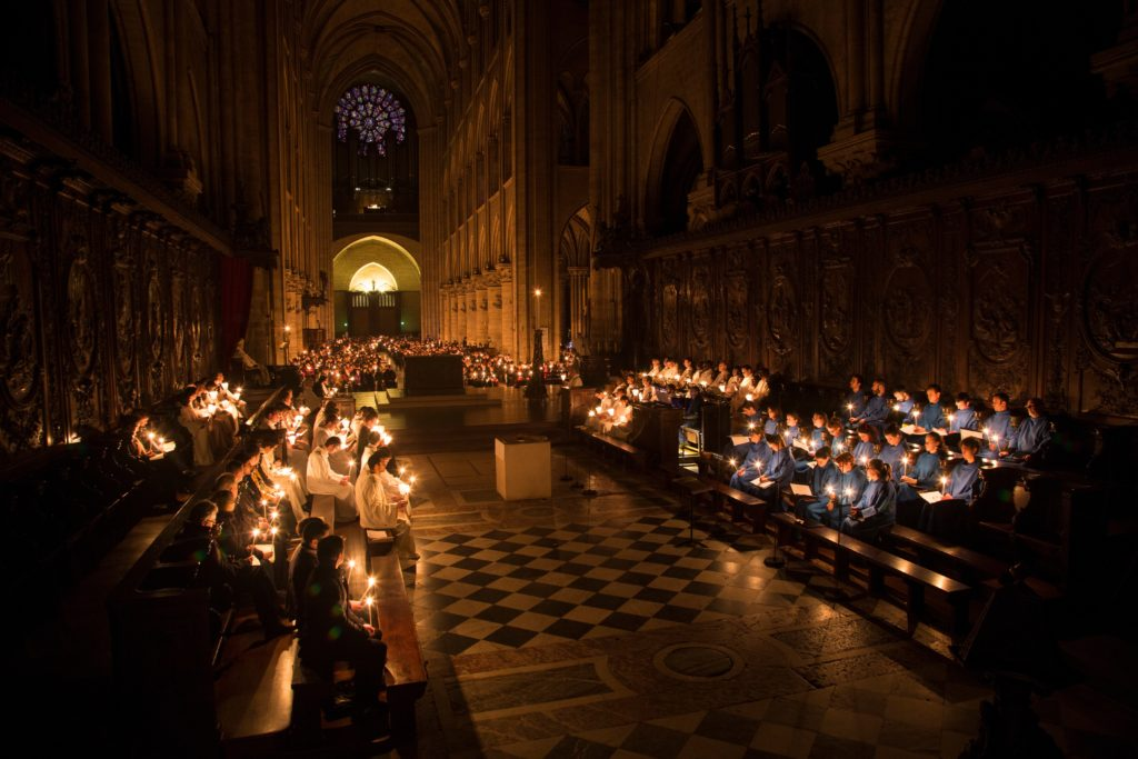 Mit Kerzenlicht in der Hand sitzen die Domchöre von Notre-Dame im Hochaltar. Ein Jahr nach der Notre-Dame-Katastrophe ist die Kathedrale immer noch eine ungesicherte Baustelle